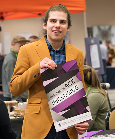 """A white person in a mustard jacket holds a purple poster that says """"This Space is Ace Inclusive"""""""