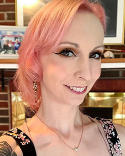 Headshot of Christie, a white cisgender woman with wavy shoulder length pink hair.