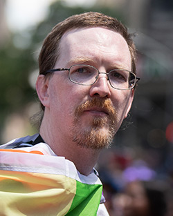 Headshot of Tom, a white man with short brown hair, a mustache, and goatee, wearing an aro flag.
