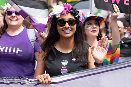 Three people march in a pride parade behind a banner. The one in front has brown skin and is waving.