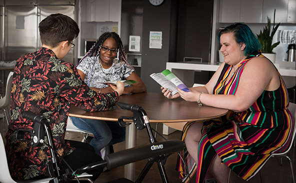 Three people in colorful clothing sit around a circular table holding pamphlets.
