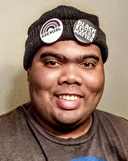 """Headshot of Marshall, a Black man wearing a beanie with """"Asexual"""" and """"Black Lives Matter"""" pins on it."""