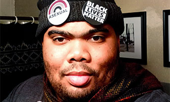 """A Black man with facial hair wearing a beanie with """"Black Lives Matter"""" and """"Asexual"""" pins holds up two fingers."""