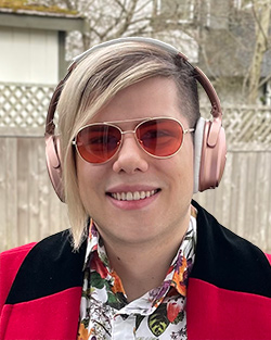 Headshot of Basil, a white nonbinary person with a blonde undercut, wearing red glasses and pink headphones.